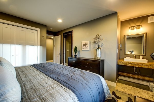 Downstairs features two bedrooms each with their own ensuite vanity sinks. Photo 10 of Ascent Estes Park modern home
