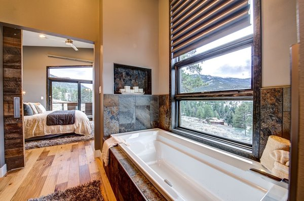 A wall lightswitch operates the LED candles in nooks flanking the air massage tub by Kohler Photo 18 of Ascent Estes Park modern home