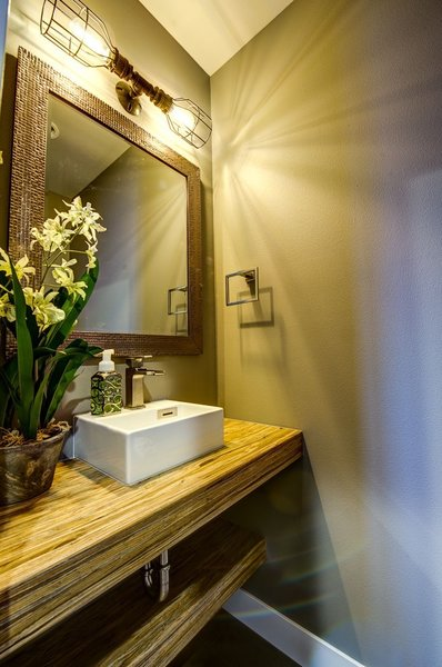 The hall powder bath features the home's signature use of Parallam beams repurposed as countertops and shelves. Photo 8 of Ascent Estes Park modern home