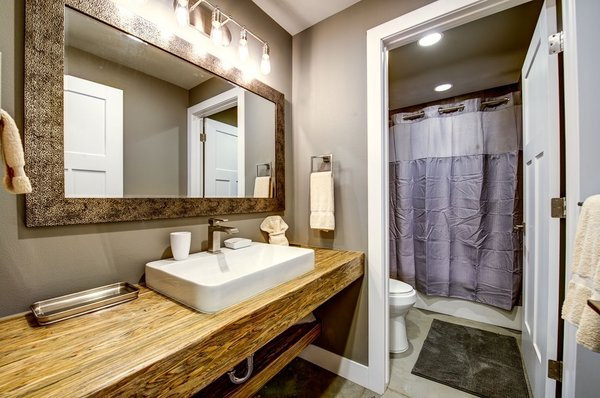 The downstairs hall bath mixes textures with Parallam countertops, concrete floors and warming gray textiles. Photo 11 of Ascent Estes Park modern home