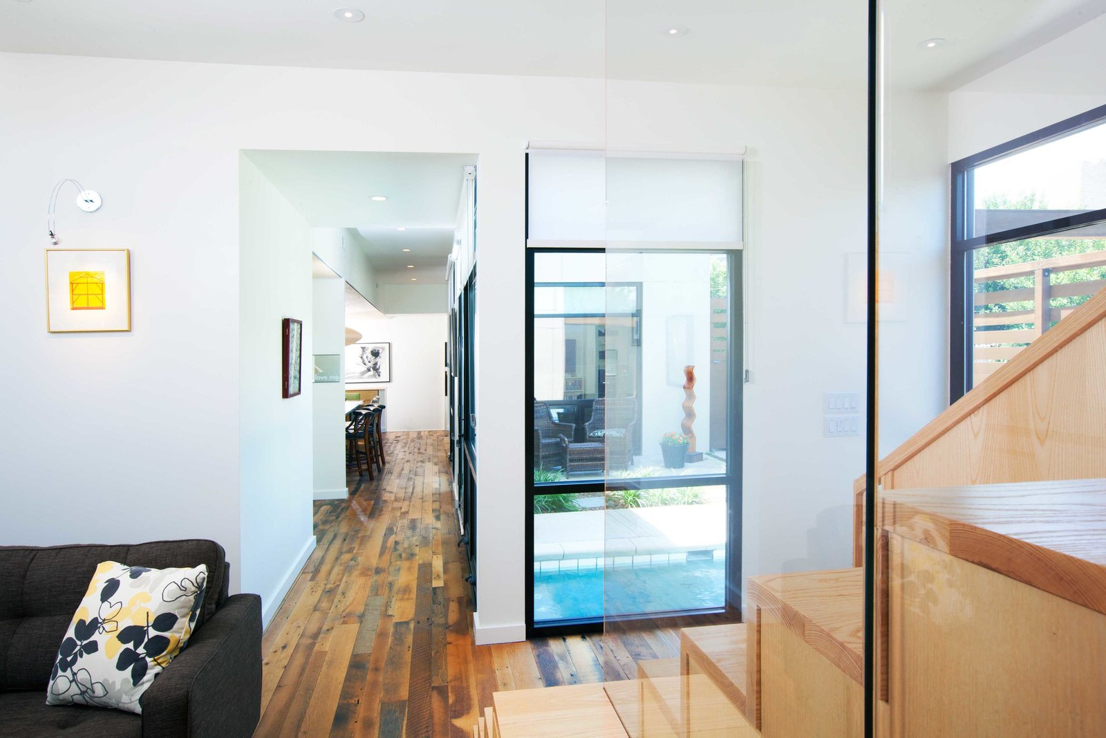 A Zen-like plunge pool situates itself at the corner of the court, visible from many areas of the house and welcomes guests along their entry journey. Tagged: Plunge Pools, Tubs, Shower, Medium Hardwood Floor, Staircase, Glass Railing, and Wood Tread.  City Cottage by ONE 10 STUDIO Architects