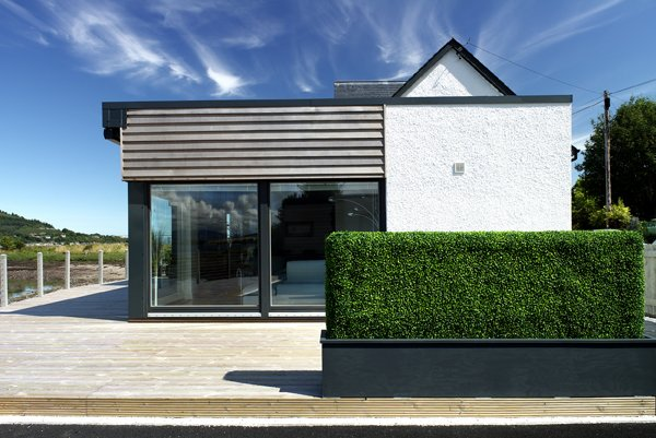 This former fisherman's cottage on the Caledonian Canal was transformed in 2009 by Reynolds Architecture Ltd., which implemented an open plan layout that faces the ocean. Timber cladding and large windows unite with the historic façade of the home. Tagged: Exterior, House, Wood Siding Material, and Glass Siding Material.  Photo 5 of 11 in Merging Old and New With These 10 Modern Renovations in Scotland