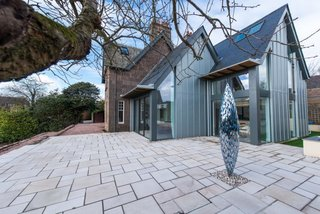 Merging Old and New With These 10 Modern Renovations in Scotland - Photo 5 of 10 - In 2016, Hyve Architects completed the renovation of The Gables, a heritage home in Stonehaven. A modern extension features an open kitchen and family room that connects to the main stone home. The double-pitched roofline of the new structure references the end gable line of the original house.