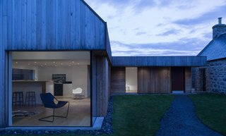 Merging Old and New With These 10 Modern Renovations in Scotland - Photo 8 of 10 - This previously abandoned granite, 18th-century farmhouse in the Scottish Highlands was restored and extended by Moxon. The addition—that's clad with larch and red metal—references the gabled roofline of the original structure and is connected via a glass passageway.