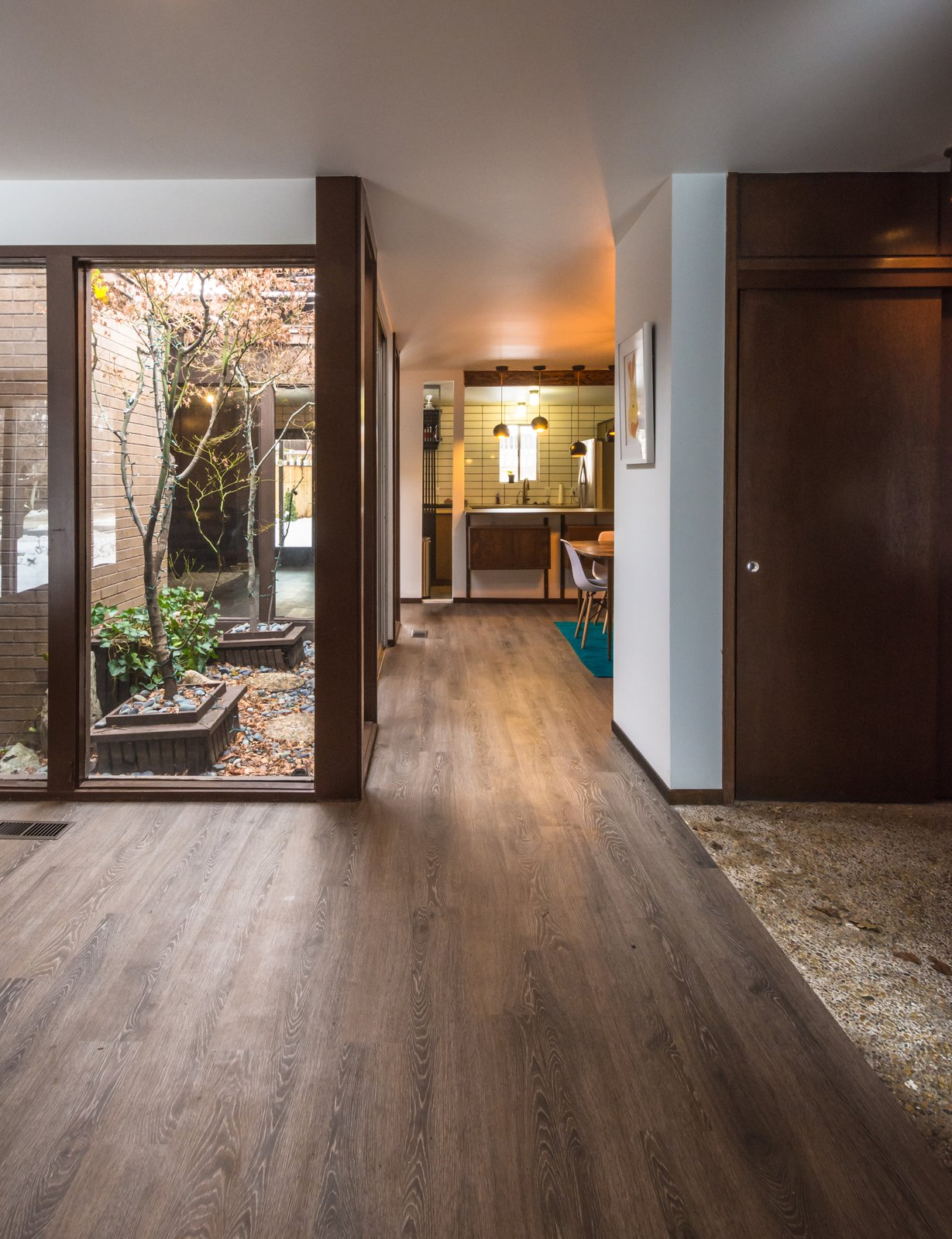 Entry showing the view all the way back to the dining and kitchen area with lots of light from the atrium. Note aggregate flooring at entry  Ron Molen Revival by The Muve Group