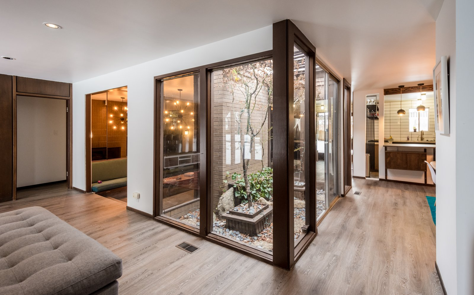 Entry of home showcasing the original atrium new flooring and open floor plan  Ron Molen Revival by The Muve Group