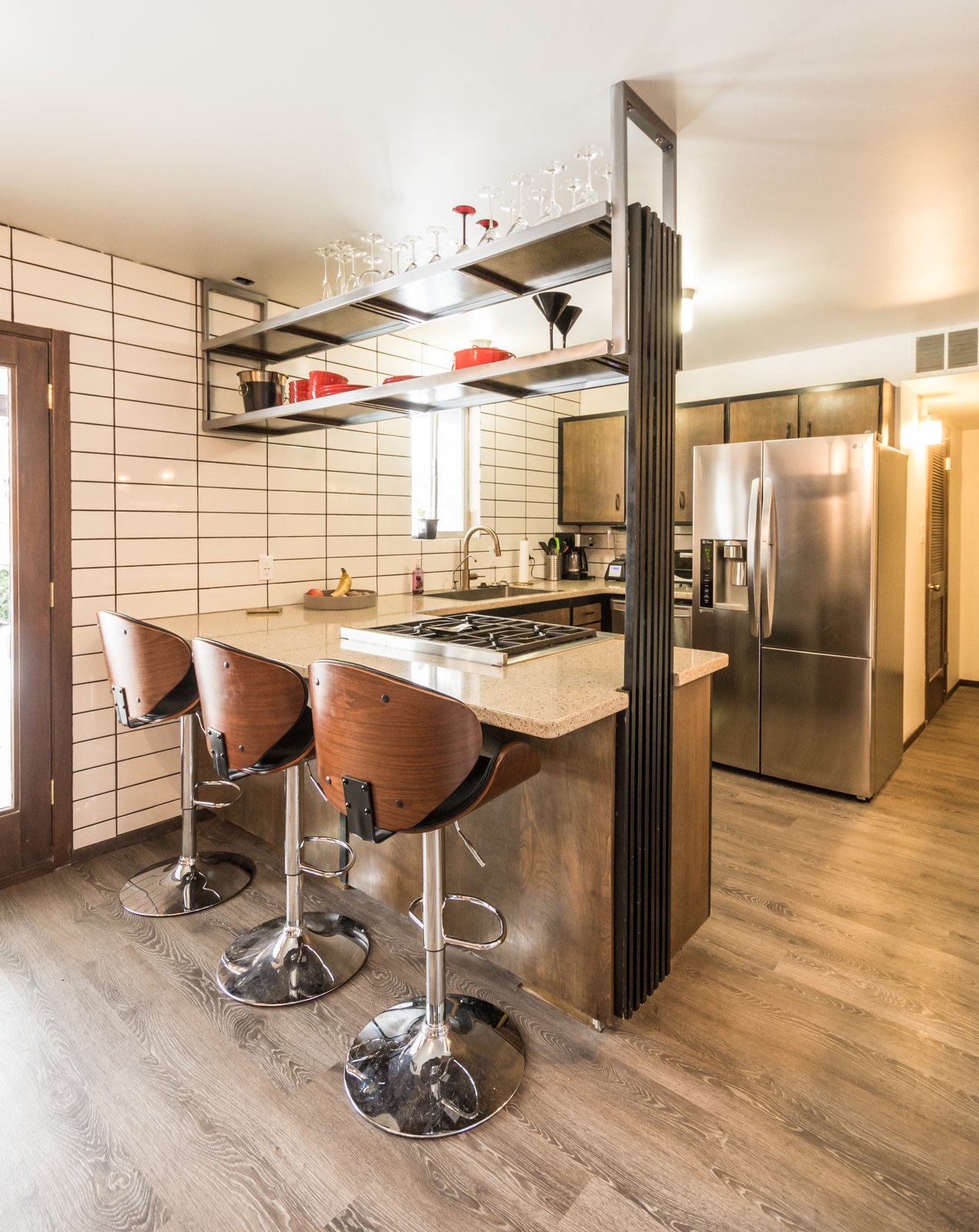 Original kitchen cabinets with new appliances, updates shelf hung from ceiling and full height back splash and original repurposed vertical wood slats  Ron Molen Revival by The Muve Group