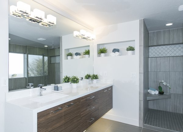 """This master bathroom has been outfitted with a floating vanity, under cabinet lights, back lit mirrors, a glass shower door, soaking tub and of course, a """"throne room"""".  King of the Wasatch by The Muve Group"""