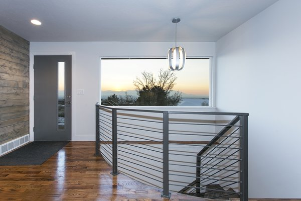 The front entry has a equal blend of oak, cedar and steel railing that creates a great space to soak in the Salt Lake Valley views of the Oquirrh mountain range. Photo 12 of King of the Wasatch modern home