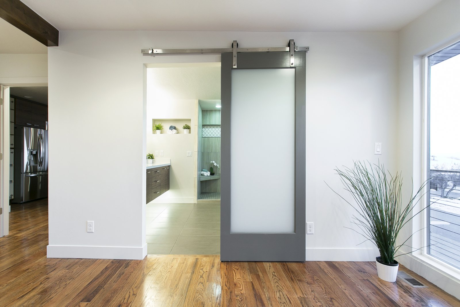 This perfectly placed barn door leads from the master bedroom to the newly renovated modern bathroom with floating cabinets and under cabinet lighting.  King of the Wasatch by The Muve Group