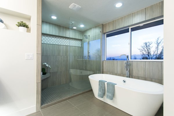 The master bathroom has been fully reworked to capitalize on the sweeping views that can be seen not just from the master bedroom but out the window perched directly above the soaking tub. Photo 4 of King of the Wasatch modern home