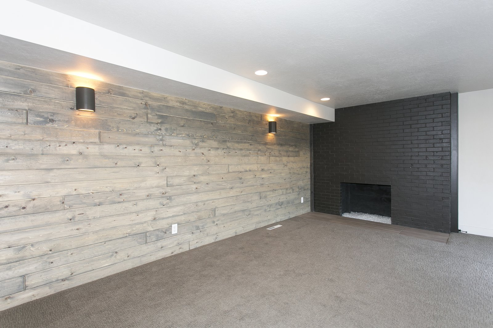 Basement Family room with wood accent wall and painted black brick fireplace.