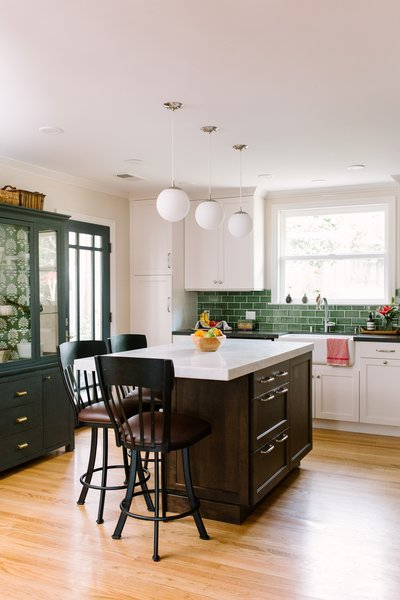 A large dark wood stained island provides extra storage and work space for both the parents and the children.