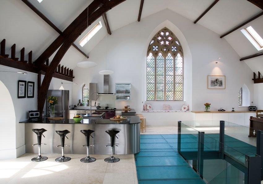 In Kelso, Scotland, a centuries-old stone church was converted into a five-bedroom house where the upper floor of the church is one large, open space that houses a kitchen, dining area, living room, and games space.  Photo 9 of 9 in 7 Repurposed Churches Around the World