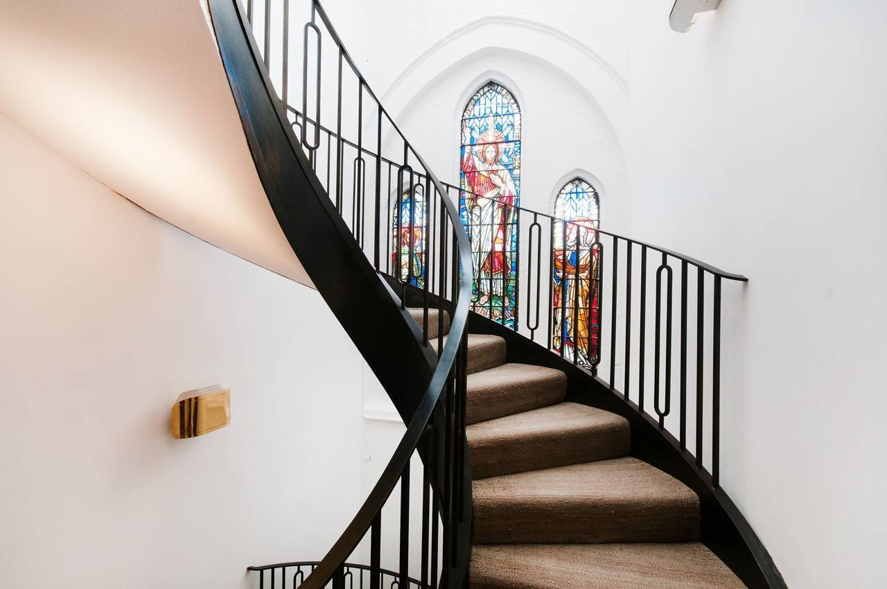 In London, a brick church's stained glass windows provide a pop of color, in contrast to the surrounding stark white walls and black powder-coated steel spiral stair.
