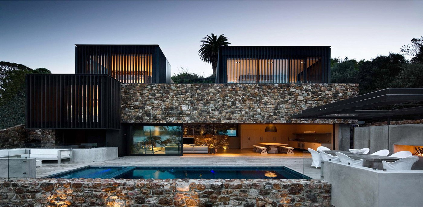 Stone walls surround the patio area and the edge of the pool. Tagged: Exterior, House, and Stone Siding Material.  Photo 2 of 16 in These 4 Modern Homes Around the World Take Advantage of Local Stone