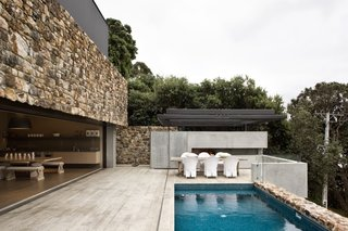 These 4 Modern Homes Around the World Take Advantage of Local Stone - Photo 3 of 16 - Stone walls surround the patio area and the edge of the pool.