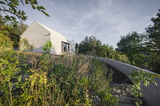 These 4 Modern Homes Around the World Take Advantage of Local Stone - Photo 6 of 16 - The approach to the home is defined by a concrete wall and gravel path.
