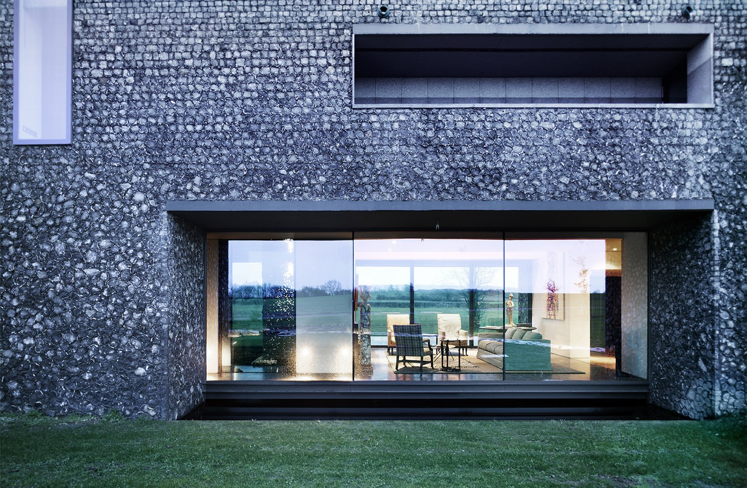 A dark, almost black mortar on the lower portion of the home makes it feel grounded in the landscape. Tagged: Windows.  Photo 11 of 16 in These 4 Modern Homes Around the World Take Advantage of Local Stone