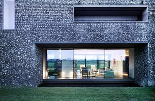 These 4 Modern Homes Around the World Take Advantage of Local Stone - Photo 11 of 16 - A dark, almost black mortar on the lower portion of the home makes it feel grounded in the landscape.
