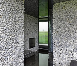 These 4 Modern Homes Around the World Take Advantage of Local Stone - Photo 12 of 16 - On the upper floor, smaller stones of lighter colored flint cover the walls.