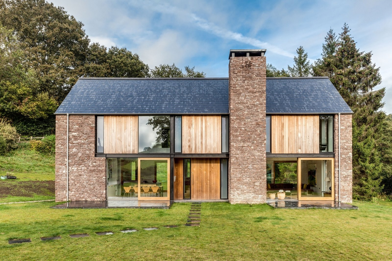 The other facades have wood panels as well as the local red sandstone.  Photo 16 of 16 in These 4 Modern Homes Around the World Take Advantage of Local Stone