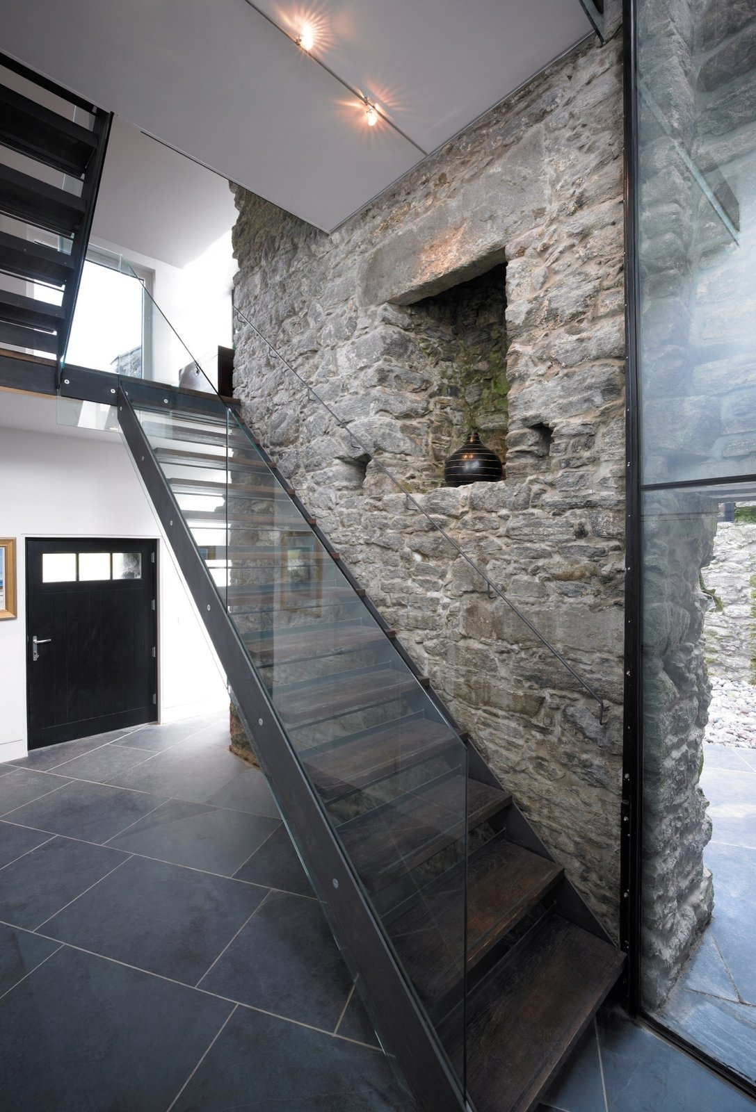 On the interior, existing stone walls are often left exposed Tagged: Staircase, Wood Tread, and Glass Railing.  Photo 5 of 19 in Rising From the Ruins: Homes Built on Architectural Remains