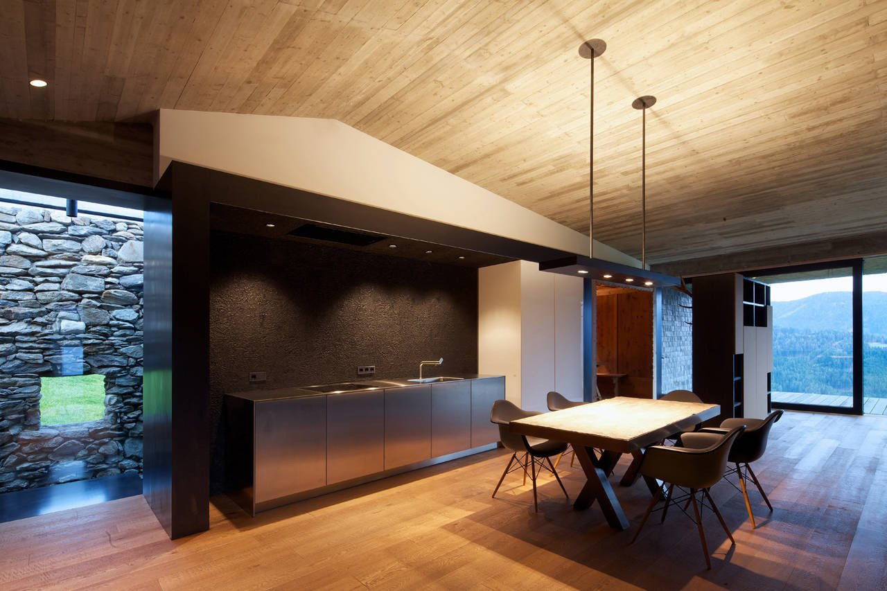 On the interior, views of both the old stone wall and the landscape beyond are emphasized. Tagged: Kitchen, Stone Tile Backsplashe, Medium Hardwood Floor, and Track Lighting.  Photo 9 of 19 in Rising From the Ruins: Homes Built on Architectural Remains