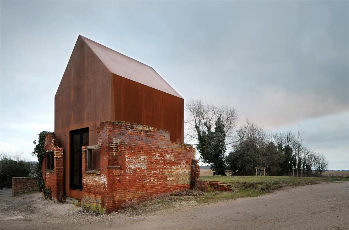 The contrast between the old, dilapedated brick structure and the new, smooth Corten steel create a balance between the old and new. Tagged: Exterior, Gable RoofLine, Brick Siding Material, Tiny Home Building Type, Metal Roof Material, Metal Siding Material, and Shed Building Type.  Photo 12 of 19 in Rising From the Ruins: Homes Built on Architectural Remains
