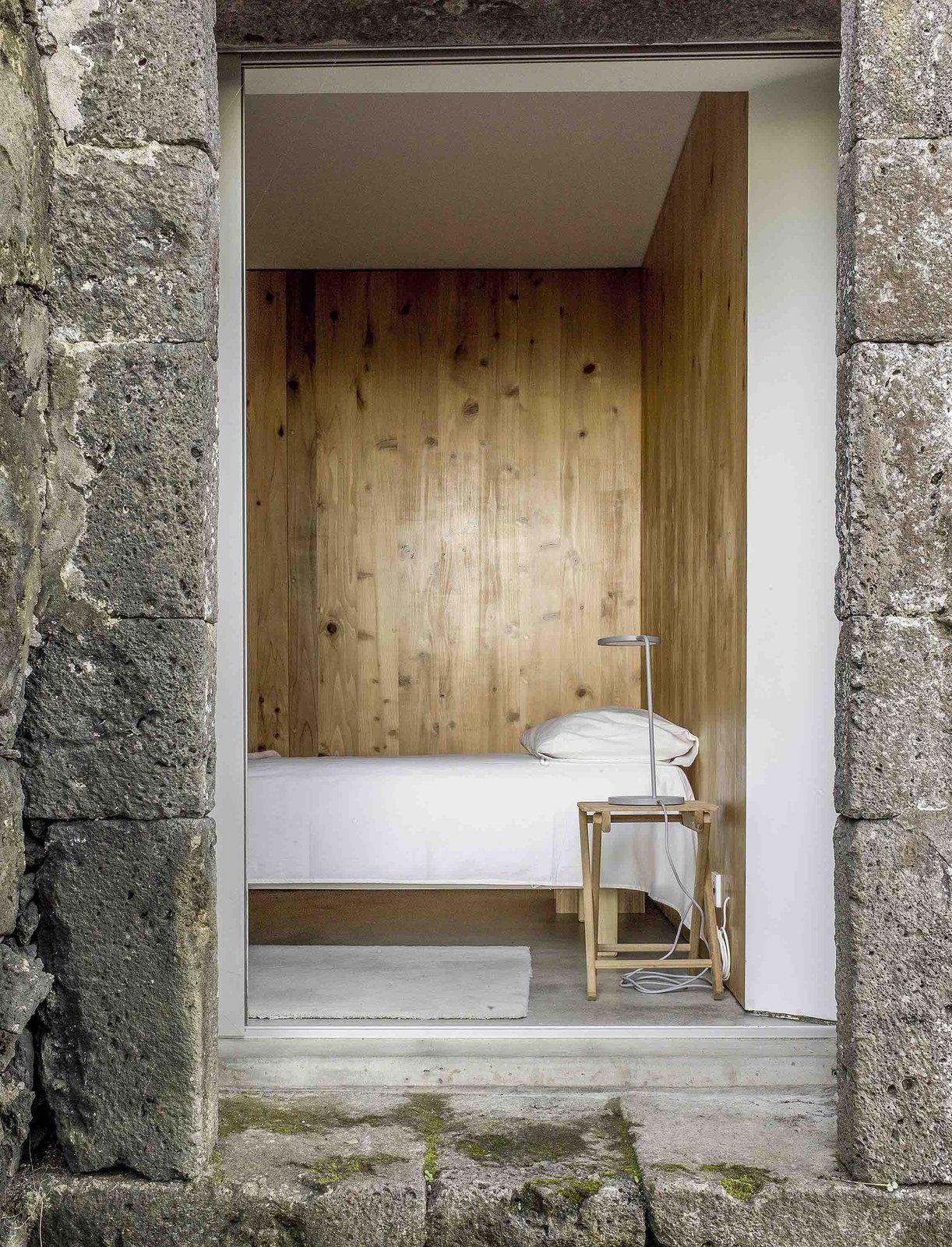 When openings in the new and the old building are aligned, the framed views capture new and old and let in light and air. Tagged: Bedroom, Bed, Night Stands, and Concrete Floor.  Photo 18 of 19 in Rising From the Ruins: Homes Built on Architectural Remains