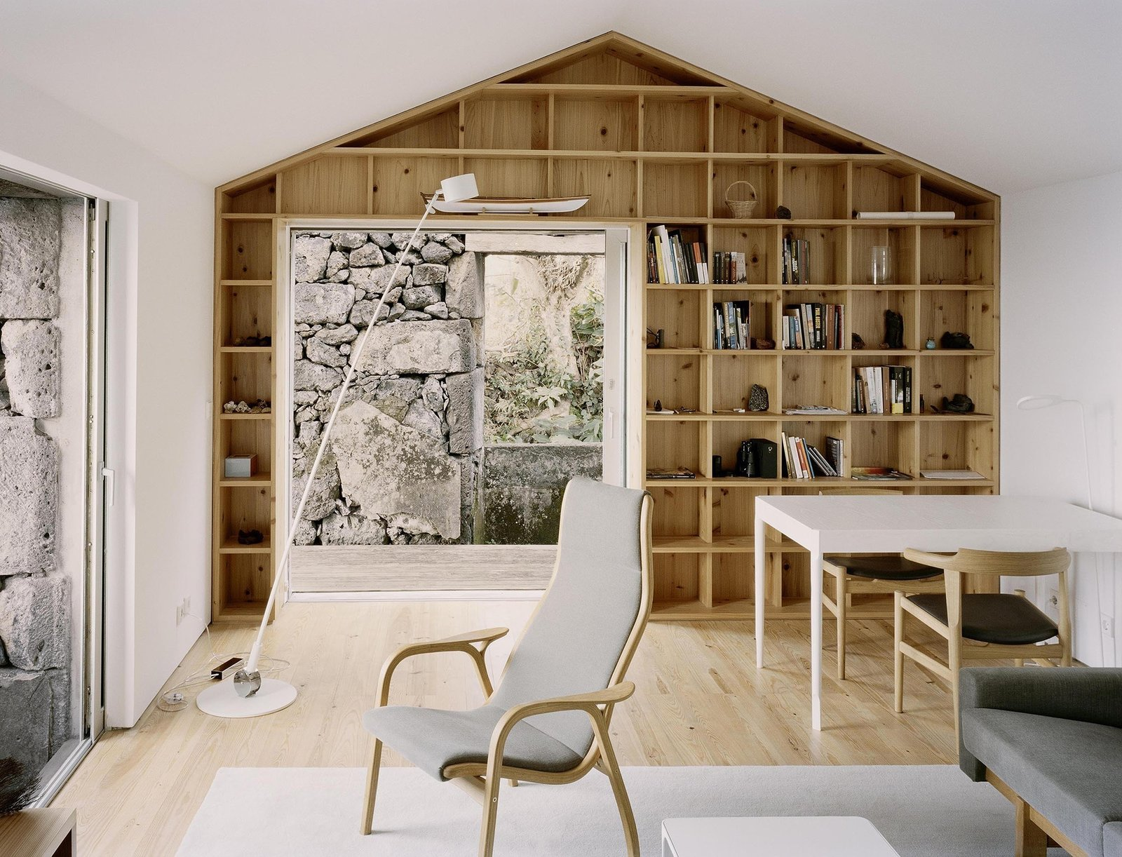 The interiors frame selective views of the existing rock walls, and contrast them with light finishes of white walls and wood furniture and shelving.