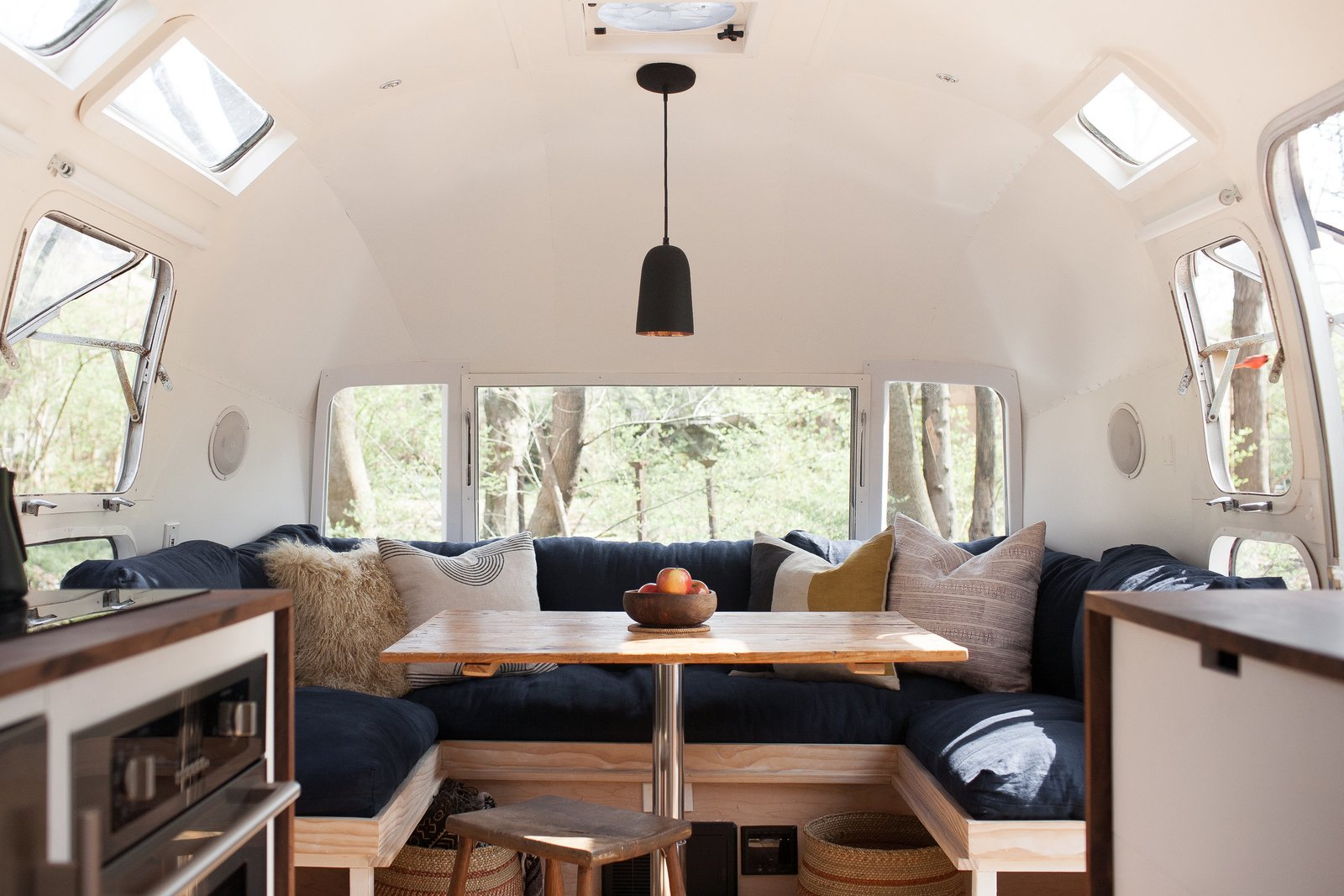 Ellen Prasse, an art teacher, and her partner, artist and writer Kate Oliver, transformed their lives and this 1977 Airstream over the course of a year, bringing the trailer back to life and giving it a classic but modern redo. Small touches, like a matte black faucet and light fixture paired with stainless steel appliances, along with a mixing of dark and light wood finishes prevent the space from feeling too matchy-matchy and overwhelming. Tagged: Dining Room, Bench, Pendant Lighting, Table, and Stools.  Photo 2 of 8 in These 7 Vintage Airstreams Were Transformed Into Modern Escapes