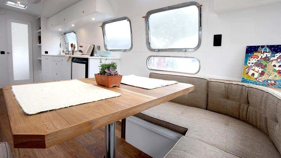 The late 1970s might be known for their bright colors and disco balls, but this 1978 Airstream remodeled by Hofman Architecture is the perfect picture of modern serenity. A combination of natural materials like raw wood and textured fabric with sleek white walls and cabinet make it feel spacious and calming. Wide-plank wood flooring gives it a rustic, warm touch, while custom-made cabinetry ensures that every inch is used.  Photo 1 of 8 in These 7 Vintage Airstreams Were Transformed Into Modern Escapes