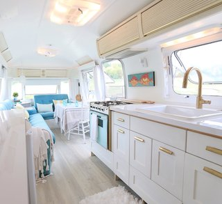 These 7 Vintage Airstreams Were Transformed Into Modern Escapes - Photo 4 of 8 - By consistently using brushed-gold hardware, tufted blue seating (which even appears to be original!), and casually-thrown fringed blankets, the space is packed with effortless personality. Light-colored wide plank wood flooring and white paint keep the space light and airy.