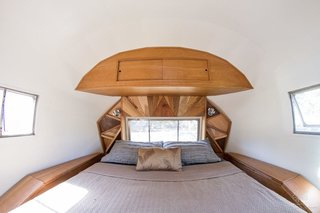 These 7 Vintage Airstreams Were Transformed Into Modern Escapes - Photo 5 of 8 - A custom headboard made of triangular pieces of black walnut is the clear hero of this 1954 Airstream renovation by ArtisTree, a designer of custom tree houses and small-space homes. Because sustainability was a priority in this project, the floors are made of recycled wood (treated with the Japanese burning technique, shou-sugi-ban, to darken them), and the tiles in the bathroom are created from recycled glass.