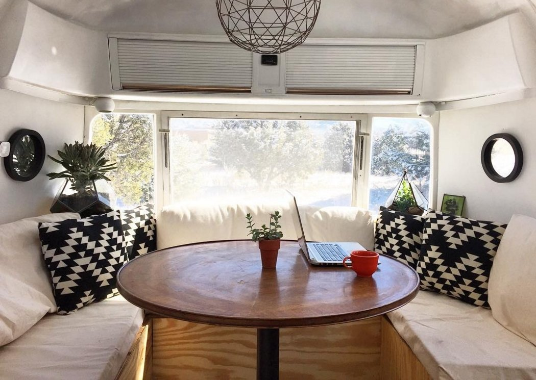 Melissa and Rusty Miller renovated their 1979 Airstream themselves, using recycled pallets for countertops and plywood for the dining area benches. In smaller spaces, it's easy to get overpowered by bright colors and bold prints, so the Millers kept their palate simple and neutral, selecting accent pillows in a striking black and white pattern to make a statement. Small, understated mirrors bring in more light and even make the space feel a bit larger.