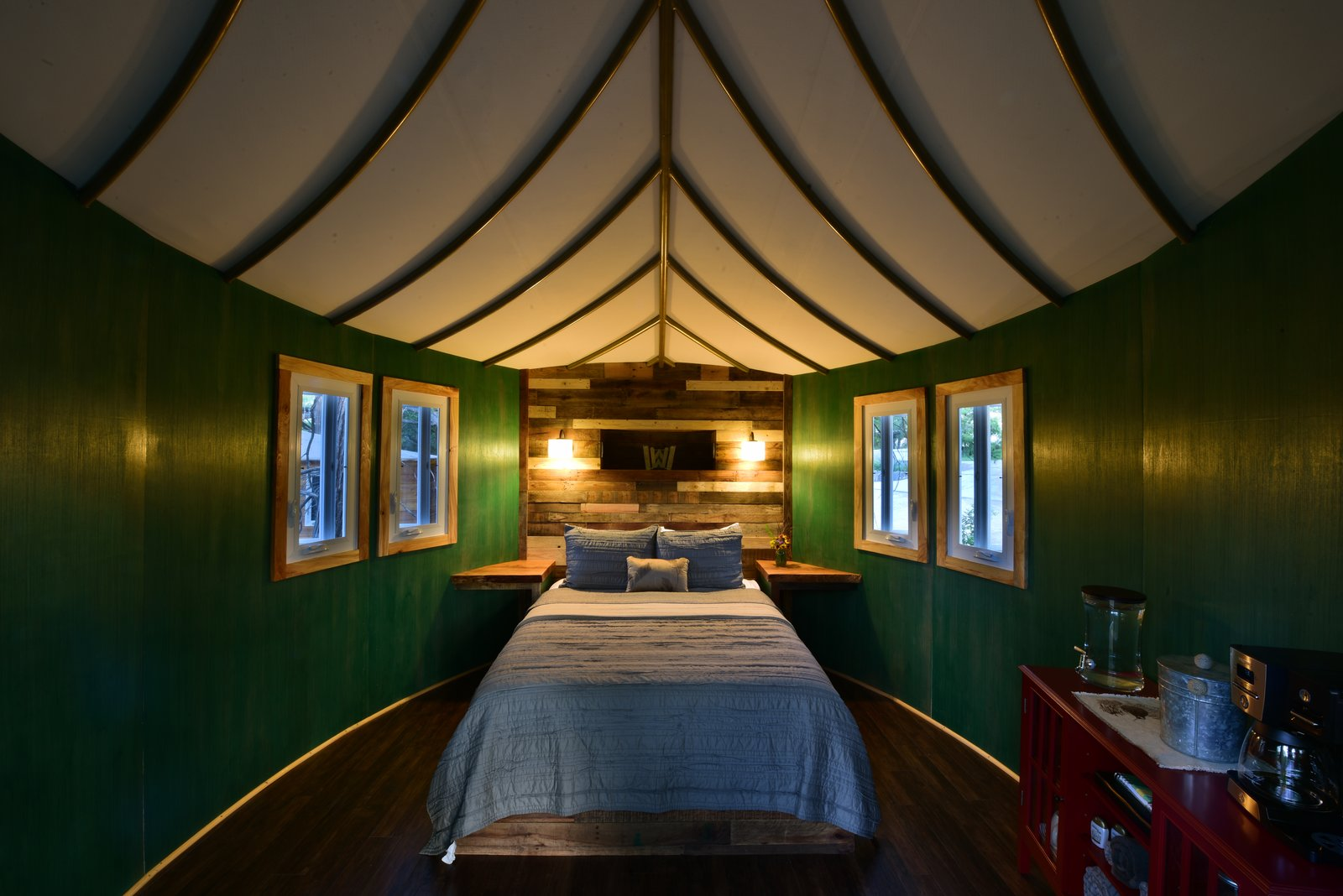 The Willow & Juniper tree house by ArtisTree Tagged: Bedroom, Wall Lighting, Bed, Night Stands, Storage, and Dark Hardwood Floor.  Photo 5 of 16 in Experience Tree-Top Living at One of These Sustainable Tree Houses