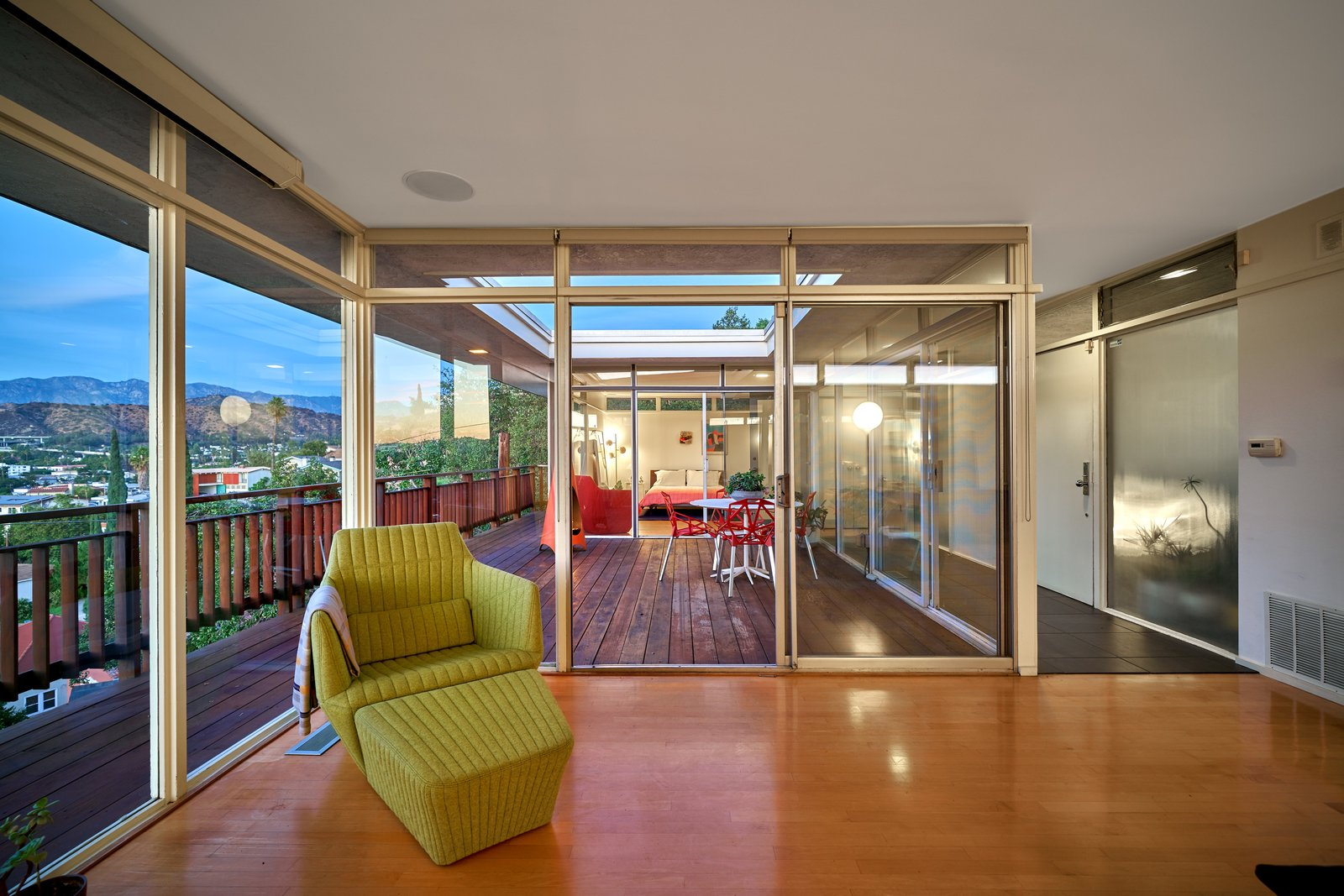 Sliding glass doors with glass transoms above maximize sunlight. Tagged: Doors, Exterior, Sliding Door Type, Metal, and Interior.  Photo 7 of 14 in A Midcentury-Modern Home in L.A. Designed by Richard Banta Is For Sale For $899K