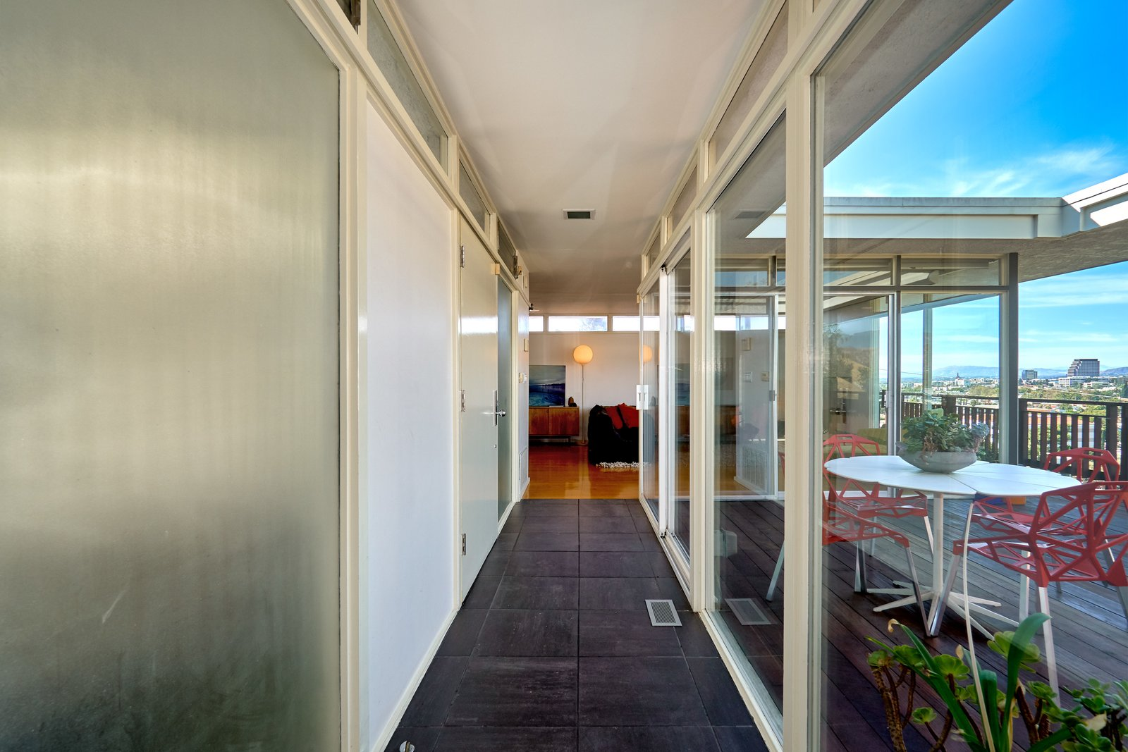 A narrow hallway with black slate tiles connects the two wings of the house. Tagged: Hallway and Cement Tile Floor.  Photo 10 of 14 in A Midcentury-Modern Home in L.A. Designed by Richard Banta Is For Sale For $899K