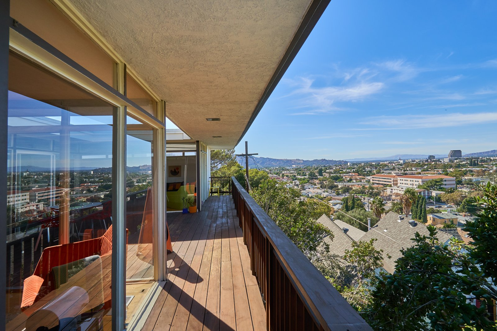 The rear of the house opens out to the rest of the city, while the facade facing the street is more closed off. Tagged: Outdoor and Wood Patio, Porch, Deck.  Photo 11 of 14 in A Midcentury-Modern Home in L.A. Designed by Richard Banta Is For Sale For $899K