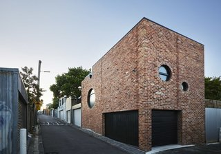 These 8 Unusual Windows Will Take You by Surprise - Photo 1 of 8 - On a rear addition to an existing suburban home outside of Melbourne, Australia, Austin Maynard Architects designed a brick structure with a series of round windows on multiple facades. The circular windows vary in size and location, giving the building a playful twist, despite its more traditional construction of red brick.