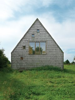 """These 8 Unusual Windows Will Take You by Surprise - Photo 2 of 8 - At this wooden A-frame retreat in the Normandy region of France, architect Jean-Baptist Barache designed a home that's both casual and elegant, low-key and surprising. A large central window on one of the end gables of the house is accompanied by a scattering of smaller, square """"peek-a-boo"""" windows. The two windows on the third floor bring light and views into the bedroom, and the window on the first floor fits perfectly into the camouflaged rear door."""