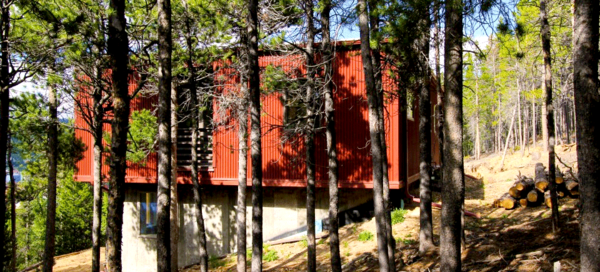 Siting closely within the surrounding pine forest, the Weehouse designed by Alchemy Architects and constructed by Irontown Homes rest only one half hour up the mountain from Boulder, CO.The tight driveway and secluded mountainside locale created an interesting delivery in which the modules were lifted by crane over the treetops and set into place. The pre-finished steel siding has been joined by a special fire protective shell due to lying in a high risk fire zone. The plethora of windows allow for natural sunlight to illuminate the warm, open interior.