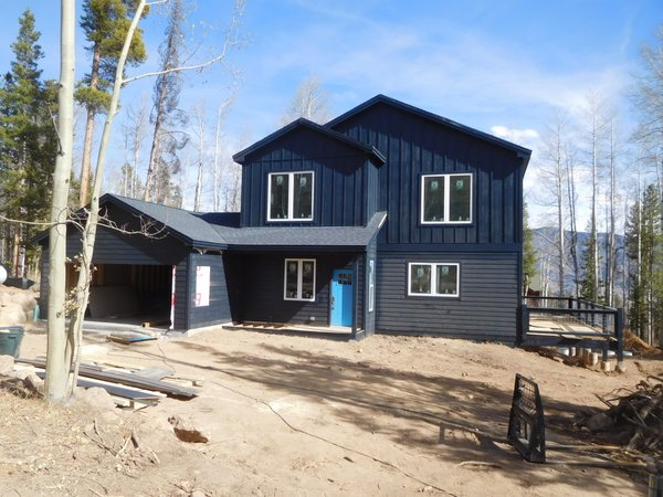 This mountain cabin by Liscott Custom Homes was designed as a three-bedroom, 3 bathroom custom build home for a family in Silverthorne, Colorado. At 2,400 square feet, the home is clad in contrasting horizontal and board and batten siding coated in a dark blue-gray finish.