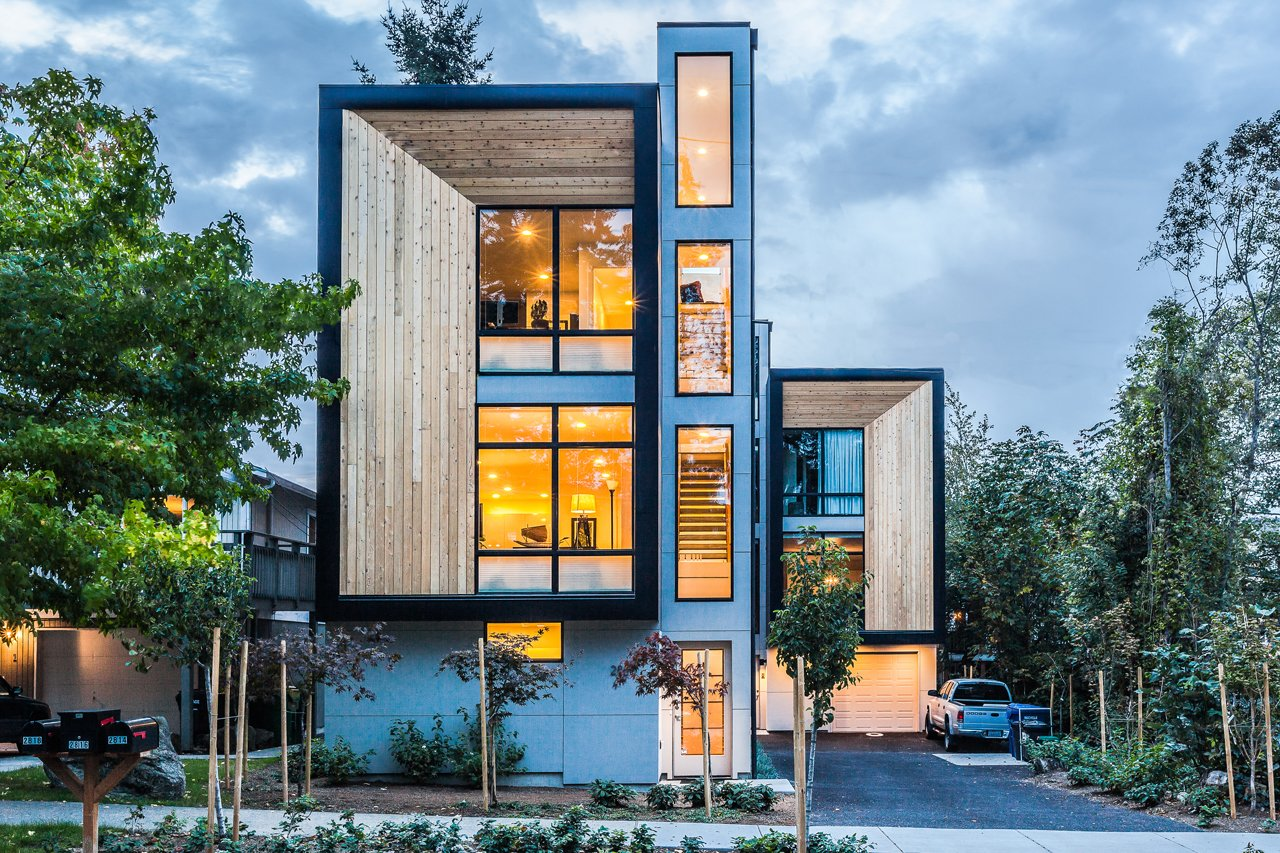 Consisting of three prefabricated units in West Seattle on a 5,000 square-foot lot, the units range from 1,250-1,400 square feet, each with three bedrooms and two and a half bathrooms. The generous glazing of the living rooms are set back from the exterior cedar rainscreen, and the rest of the facade is sheathed in metal panels. The ground floor was built onsite, but the upper two floors were prefabricated offsite in a factory.