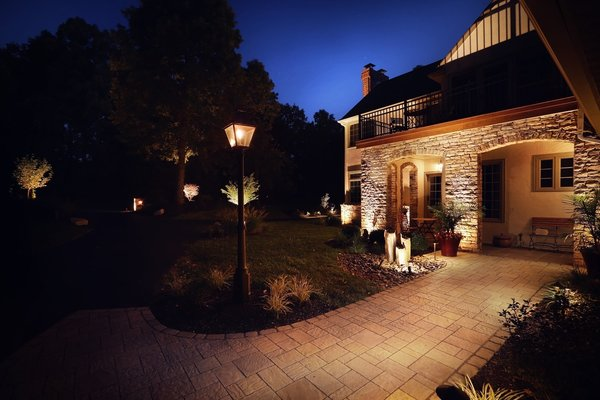 We installed a wider paver walkway, added a Bevelo handcrafted antiqued gas lantern, numerous LED lights that splashed against the stone and stucco to create an inviting side entry. Photo  of The Kalimtzis Residence modern home