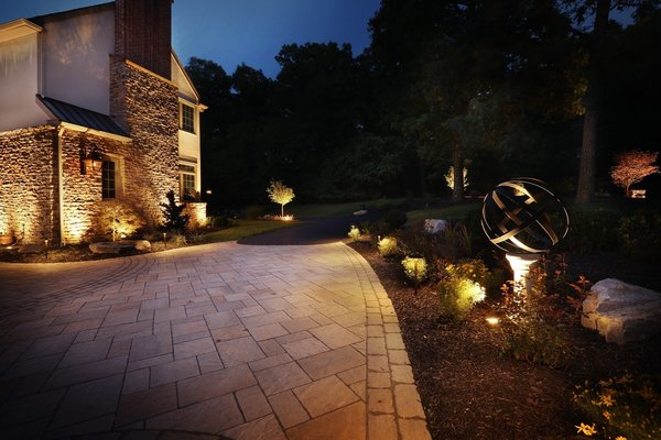 The macadam driveway was unattractive. Decorative pavers were added to the center of the driveway to break up the macadam and expand the now welcoming front walkway and entrance. Photo 2 of The Kalimtzis Residence modern home