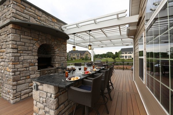 This client loves to cook, so an outdoor kitchen and dining area was essential. The grilling area uses the same chase as the lower level fireplace, which adds innovation as well as functionality. Photo 4 of The Nowak Residence modern home