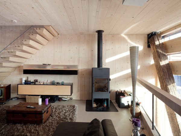 The pellet stove, in the living room area,  serves multiple purposes, providing heat for the shower and heating rooms on very cold days. Photo 5 of Energy Neutral House modern home