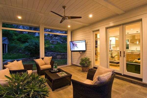 The covered porch makes for a stunning outdoor living space that is very suited for life in New England. This porch is generous in scale and extends off the open concept living areas of the Kitchen and Family room of the home. An outdoor entertainment system with surround sound and a television, built for outdoor use from SunBrite TV, makes this a great gathering space. Photo 2 of Greenwich Modern Barn modern home